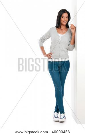 Beautiful young casual woman leaning on white wall isolated