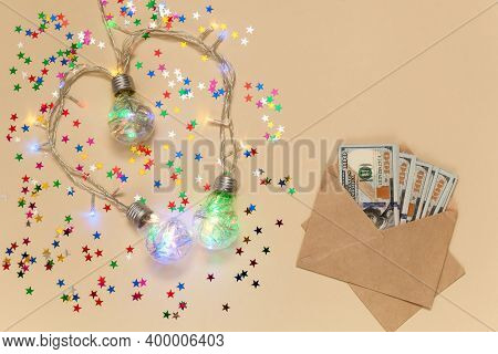 Christmas Glowing Garlands In The Form Of Light Bulbs On A Beige Background.gift Envelopes With Mone