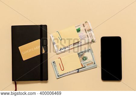 Business Concept Items On The Table Diary, Dollars, Gold Card, Phone, On A Beige Background. Bitcoin