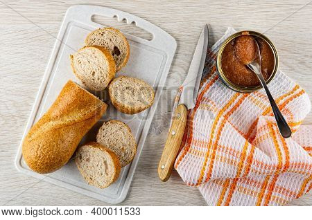 Slices Of Wheat Bread On Plastic Cutting Board, Kitchen Knife, Opened Jar With Pollock Roe On Checke