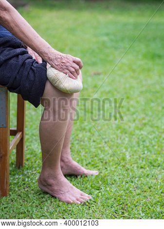 Knee Pain In A Senior Person. Senior Woman Having Knee Pain Use Thai Herbal Compress Ball On A Knee