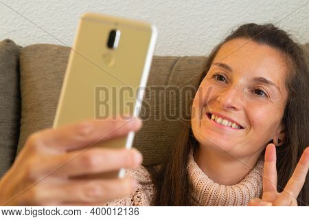 Surprised Woman Sitting On A Sofa And Covered With A Blanket Gazes Open-mouthed At Her Mobile Phone