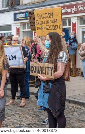 Richmond, North Yorkshire, Uk - June 14, 2020: A Girl Wearing A Face Mask Holds An Equality Banner A