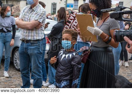 Richmond, North Yorkshire, Uk - June 14, 2020: A Young Boy Wearing A Face Mask Stands By His Mother