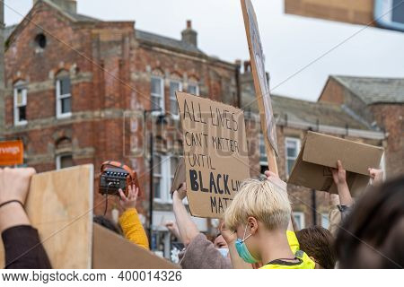 Richmond, North Yorkshire, Uk - June 14, 2020: A Black Lives Matter Placard Held Up Above A Crowd At