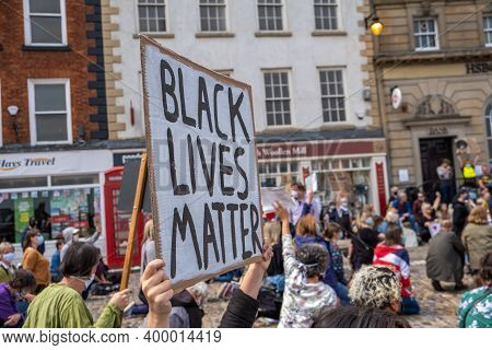 Richmond, North Yorkshire, Uk - June 14, 2020: A Black Lives Matter Placard Is Held Up Above A Kneel