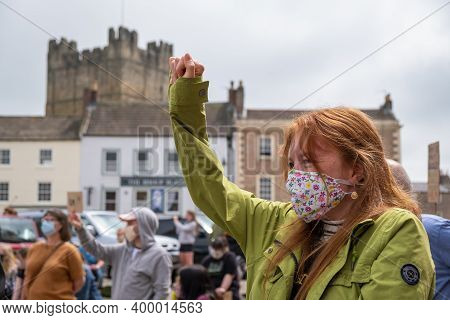 Richmond, North Yorkshire, Uk - June 14, 2020: A Powerful Girl Wearing A Face Mask Kneels With Her A