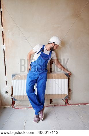 Full Length Of Bearded Young Man Plumber Checking Radiator While Installing Heating System In Apartm