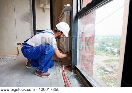 Side View Of Young Man In Work Overalls Installing Heating Radiator In Room. Male Worker In Safety H