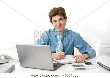 Businessman Sitting In Front Of Laptop At Office