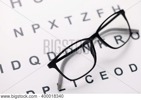 Glasses For Vision In Black Frames Lying On Test Chart Closeup. Correction Of Myopia Concept