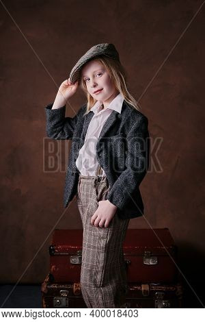 Retro Portrait Of A Little Girl In A Cap With A Visor. Suit Jacket And Pants. Brown Background