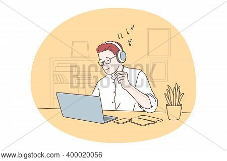 Listening To Music, Recreation Concept. Smiling Man Office Worker In Headphones Sitting With Laptop