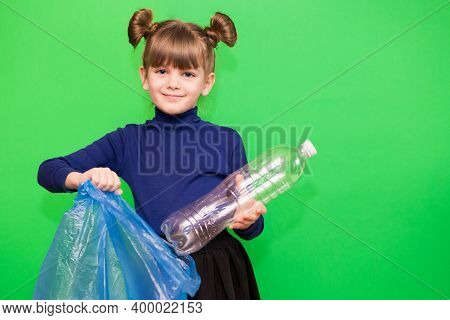 Little Cute Girl Sorting Plastic Bottles Into Trash Bag Isolated On Green Background