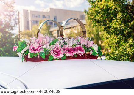 Decorative Gold Rings And Flowers For A Wedding On A White Car.