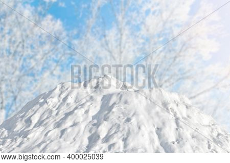 Large Snow Slide Against The Background Of Blue Sky And Trees. Winter Sunny Landscape