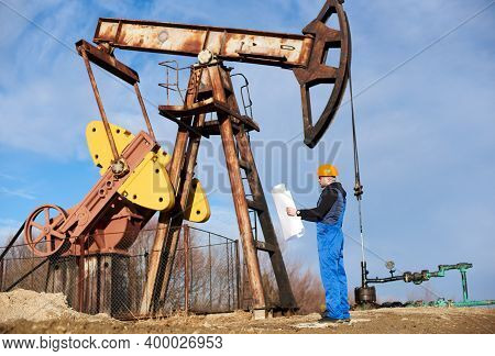 Full Length Of Oil Man Holding Placard With Oil Field Plan. Male Worker In Work Overalls And Orange