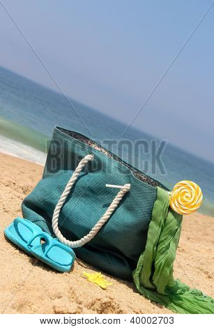 Blue Bag On The Seacoast With Lollipop