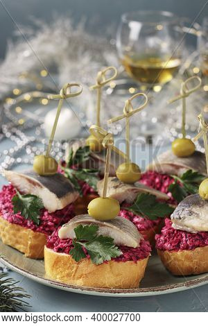 Canapes With Salted Herring, Olives And Beets On White Bread Croutons In A Plate On A Light Blue Bac
