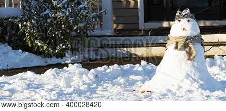 A Small Snowman On The Front Lawn Of A Residetial Home After A December Snow Fall.