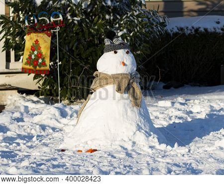 A Small Snow Man On The Front Lawn With A Carrot Nose And Wearing A Scarf And Hat.