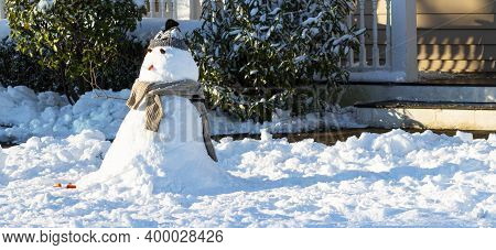 A Small Snowman In Front Of The Porch On A Front Yard In A Residential Comunity As The Sun Comes Out