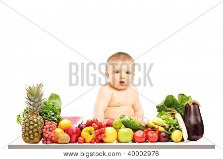 A 9 months old baby sitting on a table full of different fruits and vegetables isolated against white background
