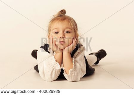 Cute Little Blond Baby Girl In Black Dress Lay On Floor