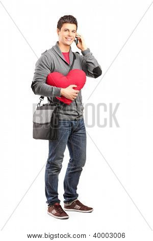 Full length portrait of a smiling student holding a red heart and talking on a phone isolated on white background