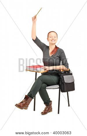 A studio shot of a female student sitting on a chair and raising her hand isolated against white background