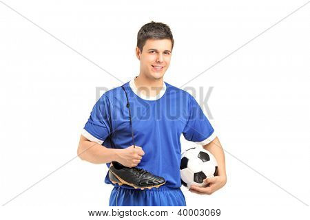 A smiling footballer in sport wear holding a soccer shoes and football isolated on white background