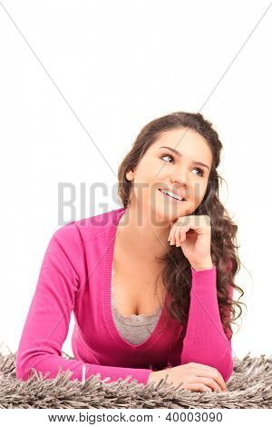 A smiling female lying on a carpet and thinking isolated on white background