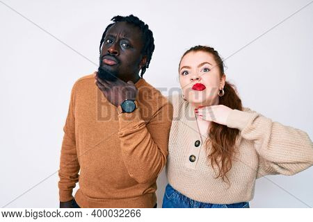 Interracial couple wearing casual clothes cutting throat with hand as knife, threaten aggression with furious violence
