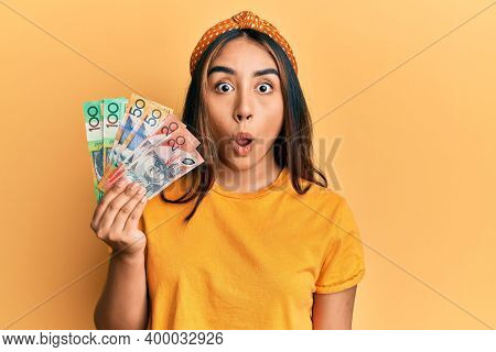 Young latin woman holding australian dollars banknotes scared and amazed with open mouth for surprise, disbelief face