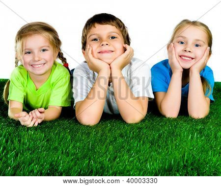 Image of happy boy and girls lying on a green grass