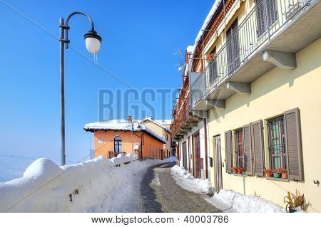 Narrow cobbled street covered with snow among lamppost and houses at town of Diano D'Alba in Piedmont, Italy.