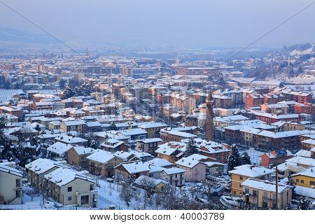 Aerial view on town of Alba among hills covered with snow at evening in Piedmont, Northern Italy.