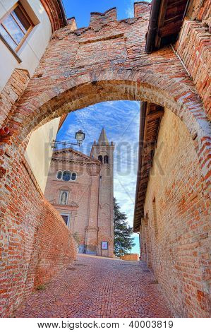 Vertical oriented image of church and medieval brick fortification wall and narrow cobbled street in town of Monticello D'Alba in Piedmont, Italy.