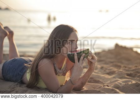 young woman eats a watermelon at the beach