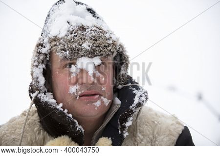 The Frozen Man In Winter Snow Fell On His Face. The First Snow Fell. A Man In A Fur Hat In Cold Weat