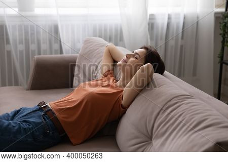Calm Young Female Reclining On Sofa With Hands Behind Head