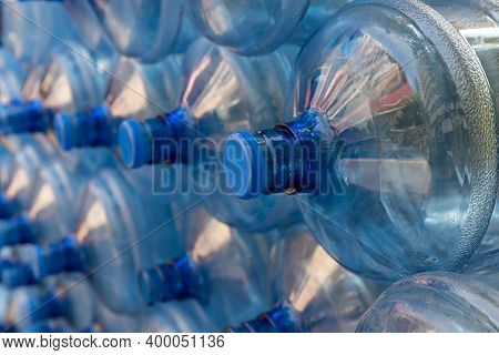 Plastic Water Bottle Background, Blue Bottle Caps, Orderly Arrangement. Empty Bottles For Drinking W