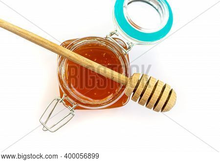 Wooden Spoon For Honey Lies On An Open Glass Jar With Floral Golden Honey On A White Background Top