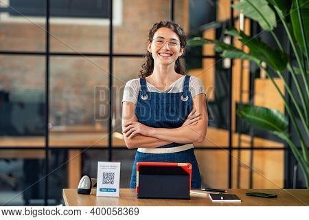 Portrait of cheerful cafe owner standing with arms crossed and digital tablet, qr code and nfc machine on table. Successful woman in cafeteria wearing apron and looking at camera. Satisfied worker.