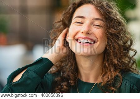 Happy young woman laughing while touching hair. Close up face of smiling girl with curly hair looking at camera. Portrait of carefree businesswoman in working in creative office with copy space.