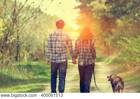 Happy Couple In Love With Dog Walking On Rural Dirt Road In Springtime At Sunset. Woman And Man Hold