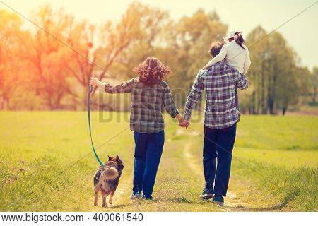 Happy Family With Dog Walking On The Rural Dirt Road On The Field. Little Girl Sitting On Dad's Shou