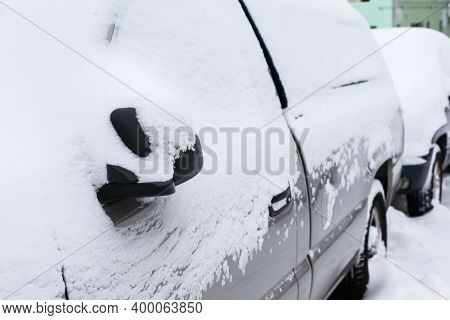 Car s covered with fresh snow in winter after storm