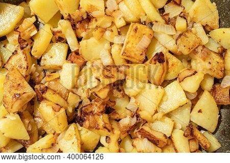 Closeup Of Appetizing Fried Potatoes With Onions On A Frypan. Shallow Dept Of Field. Selective Focus