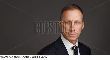 Well-groomed Middle-aged Man Portrait Against A Dark Background. Businessman Portrait. Male Headshot